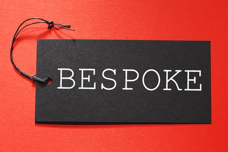 Bespoke text on a black tag on a red paper background Stock Photo