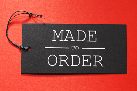 Made to Order text on a black tag on a red paper background Archivio Fotografico