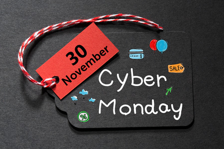 Cyber Monday November 30 text on a black tag with a red and white twine
