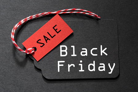 Black Friday Sale text on a black tag with a red and white twine Banco de Imagens