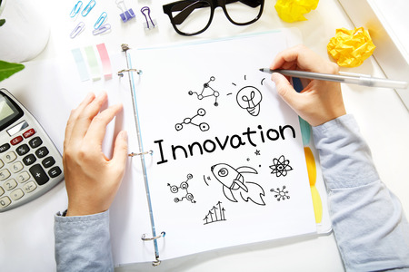 Person drawing Innovation concept on white paper in the office