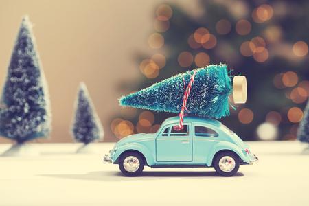 carritos de juguete: Coche que lleva un árbol de Navidad en un bosque siempre verde miniatura Foto de archivo