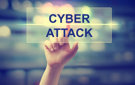 the attack: Hand pressing Cyber Attack on blurred cityscape background Stock Photo