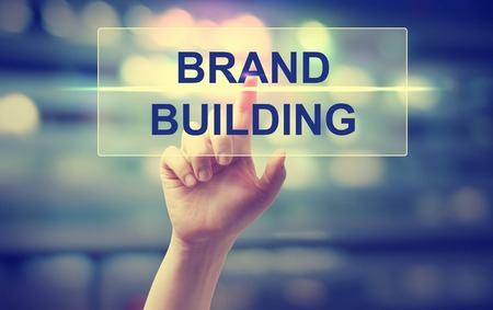 Hand pressing Brand Building on blurred cityscape background Фото со стока