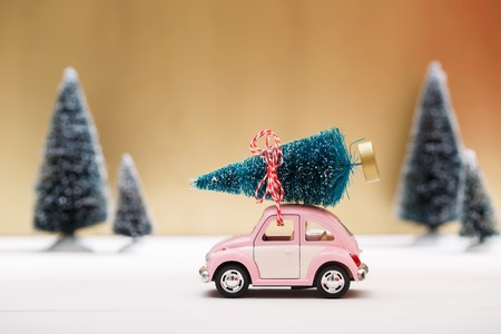 pink christmas: Car carrying a Christmas tree in a snow covered miniature evergreen forest Stock Photo