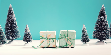 little table: Little green handmade gift boxes in a snow covered miniature evergreen forest