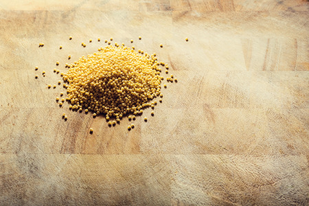 Yellow millet on a wooden rustic table