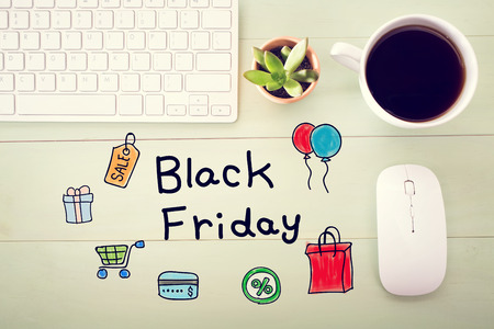 cart: Black Friday message with workstation on a light green wooden desk