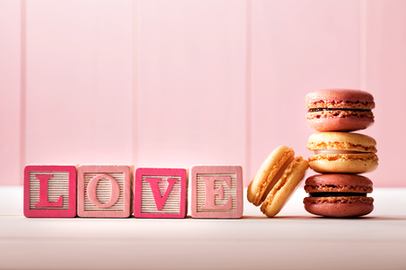 day valentine: Macarons with LOVE message on wooden blocks on pink wooden wall
