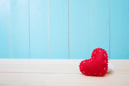 crafted: Hand crafted red felt heart on blue wood background Stock Photo