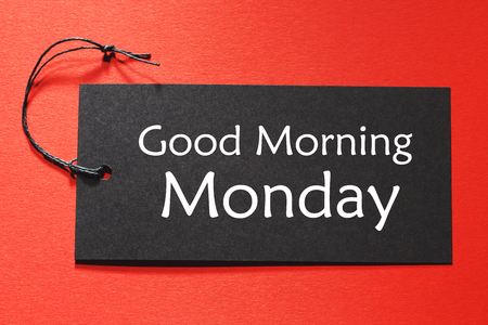 Good Morning Monday text on a black tag on a red paper background