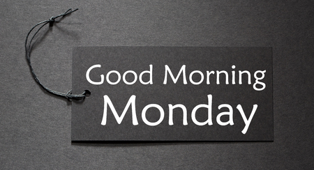 Good Morning Monday text on a black tag on black paper background