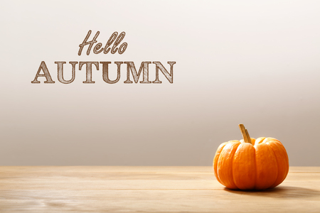 decoracion mesas: Hola mensaje de otoño con una pequeña calabaza anaranjada