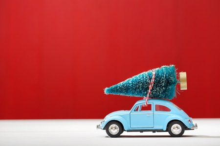 tree: Miniature car carrying a Christmas tree on red colored wooden wall