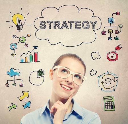 estrategia: Concepto de la estrategia con la mujer de negocios joven que llevaba gafas blancas Foto de archivo