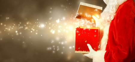 Santa Claus opening a red Christmas present on brown gold colored background Stock Photo