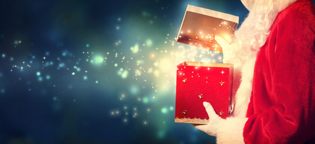 santa suit: Santa Claus opening a red Christmas present at night Stock Photo