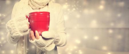 taza de t�: Mujer que sostiene una taza roja en la noche nevada Foto de archivo