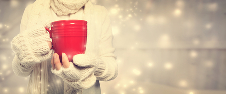 drinking of tea: Woman holding a red mug in snowy night Stock Photo