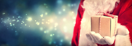 shiny suit: Santa Claus holding a gift in his hand