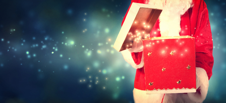 christmas costume: Santa Claus opening a red Christmas present at night Stock Photo