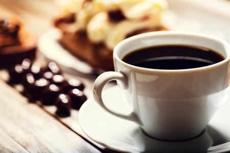 postres: Taza de café con variedad de postres en el fondo