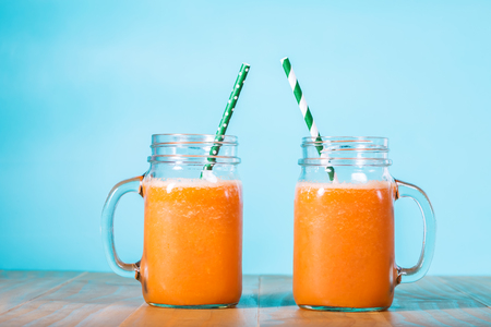 Carrot juice in masons jars on light blue background