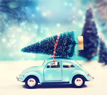 toy: Car carrying a Christmas tree in a snow covered miniature evergreen forest Stock Photo
