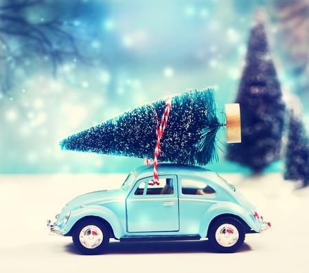 juguete: Coche lleva un árbol de Navidad en una nieve cubierto bosque siempre verde miniatura