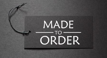 Gemaakt om tekst bestellen op een zwarte tag op zwart papier achtergrond Stockfoto