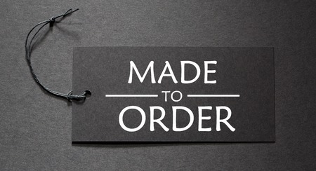 Made to Order text on a black tag on black paper background
