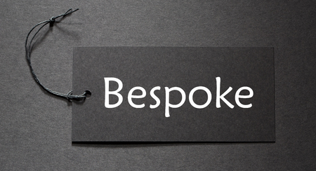 tailored: Bespoke text on a black tag on black paper background