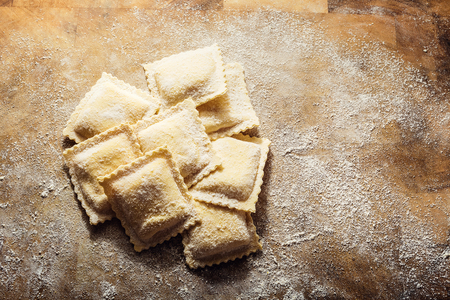 Handmade fresh ravioli on rustic wood background