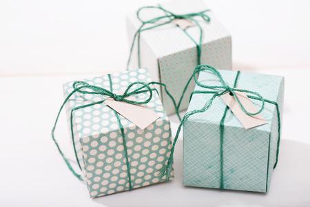 decoracion mesas: Hechos a mano pequeñas cajas de regalo verdes en mesa de madera blanca