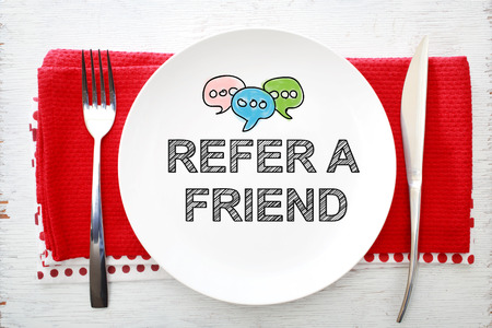 knife fork: Reffer A Friend concept on white plate with fork and knife on red napkins Stock Photo