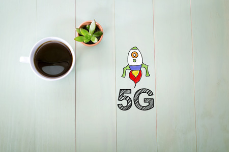 5g: 5G concept with a cup of coffee on a pastel green wooden table Stock Photo