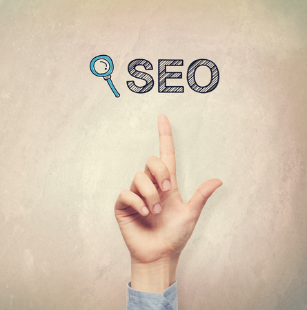 seo: Hand pointing to SEO concept on light brown wall background Stock Photo