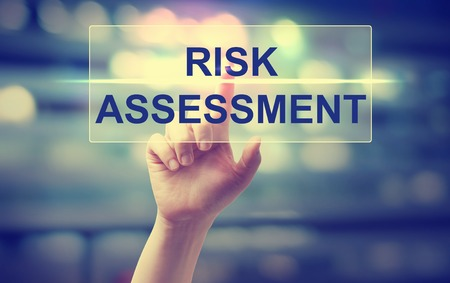 risks: Hand pressing Risk Assesment on blurred cityscape background