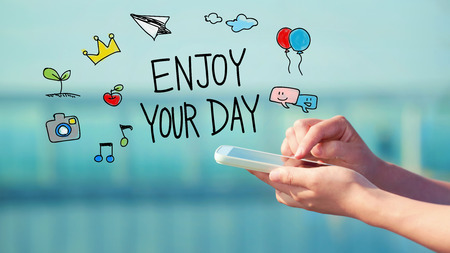 Enjoy Your Day concept with person holding a smartphone Stock Photo