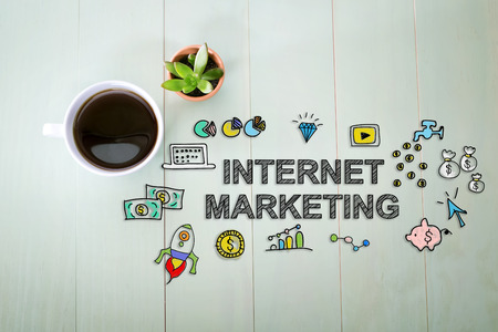 internet marketing: Internet Marketing concept with a cup of coffee on a pastel green wooden table