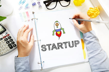 Person drawing Startup concept on white paper in the office