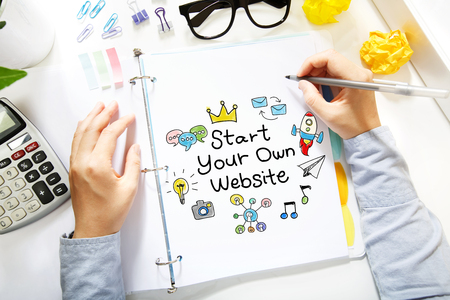 own: Person drawing Start Your Own Website concept on white paper in the office