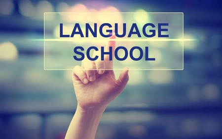 Hand pressing Language School on blurred cityscape background