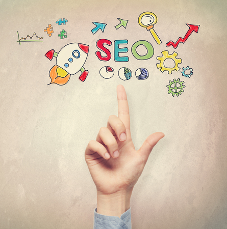 Hand pointing to SEO concept on light brown wall background Фото со стока