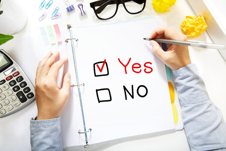 yes or no: Person drawing Yes or No concept on white paper in the office Stock Photo