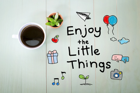 Enjoy the Little Things message with a cup of coffee on a pastel green wooden table