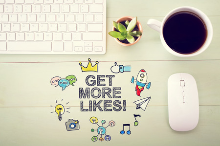 workstation: Get More Likes concept with workstation on a light green wooden desk
