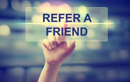 referral marketing: Hand pressing  Refer A Friend on blurred cityscape background Stock Photo