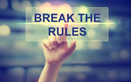 break the rules: Hand pressing Break The Rules on blurred cityscape background Stock Photo