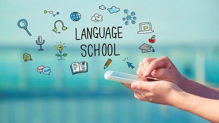 languages: Concepto de la escuela de idiomas con persona que tenga un teléfono inteligente